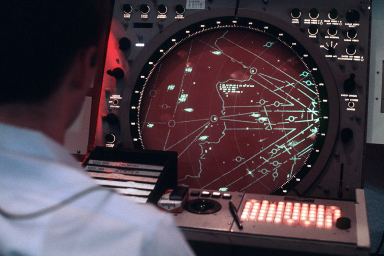 1280px-An_airman_monitors_the_new_display_console_for_the_AN-FPS-117_air_defense_radar_system_at_Templehof_Central_Airport_DF-ST-88-04934